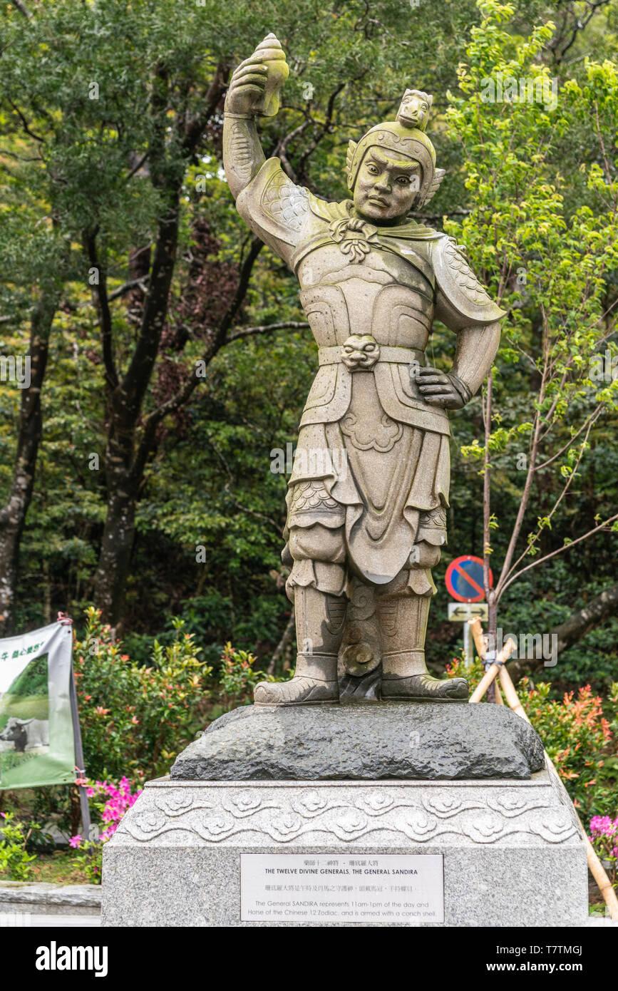 Hong Kong, China - March 7, 2019: Lantau Island. Po Lin Buddhist Monastery. Stone statue of General Sandira, one of the twelve Divine Generals. Green  - Stock Image
