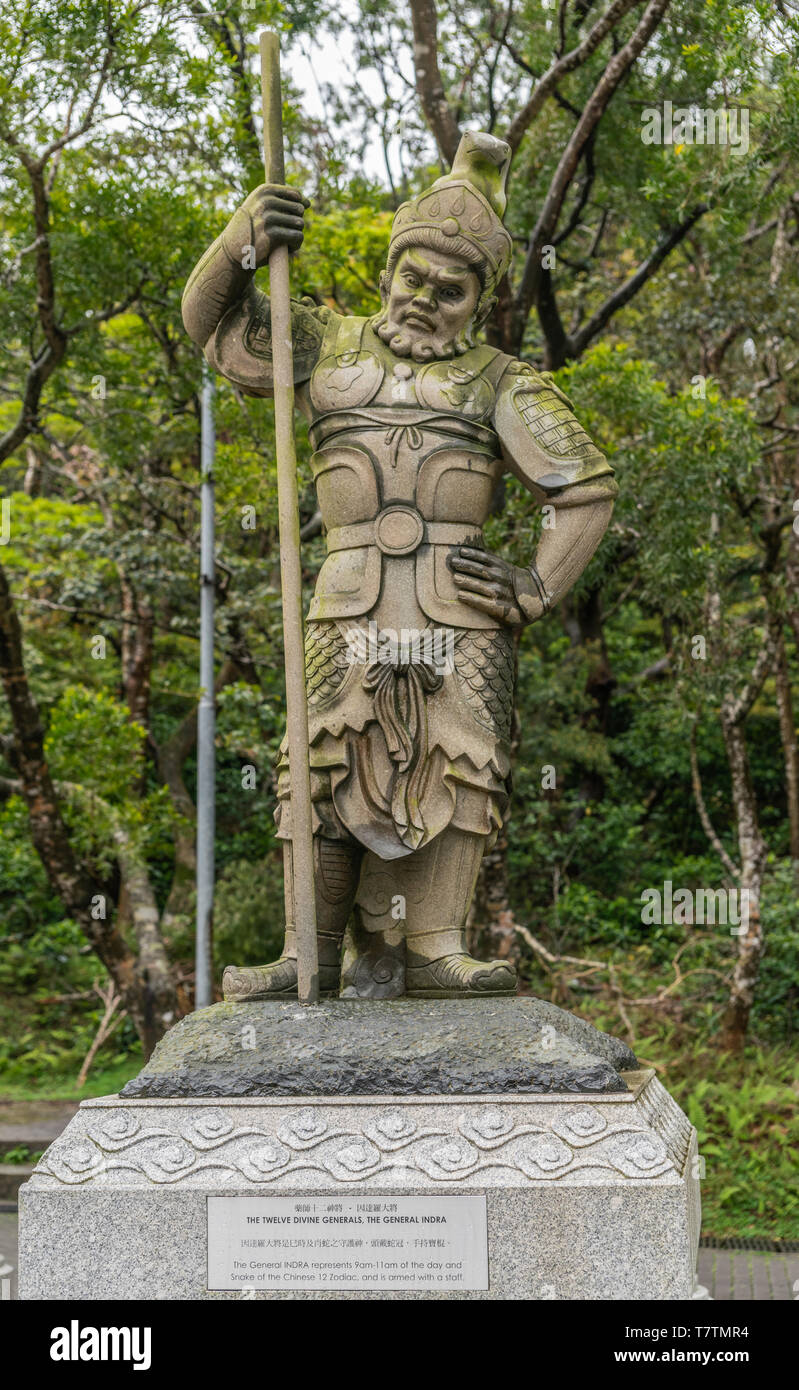 Hong Kong, China - March 7, 2019: Lantau Island. Po Lin Buddhist Monastery. Stone statue of General Indra, one of the twelve Divine Generals. Green fo - Stock Image