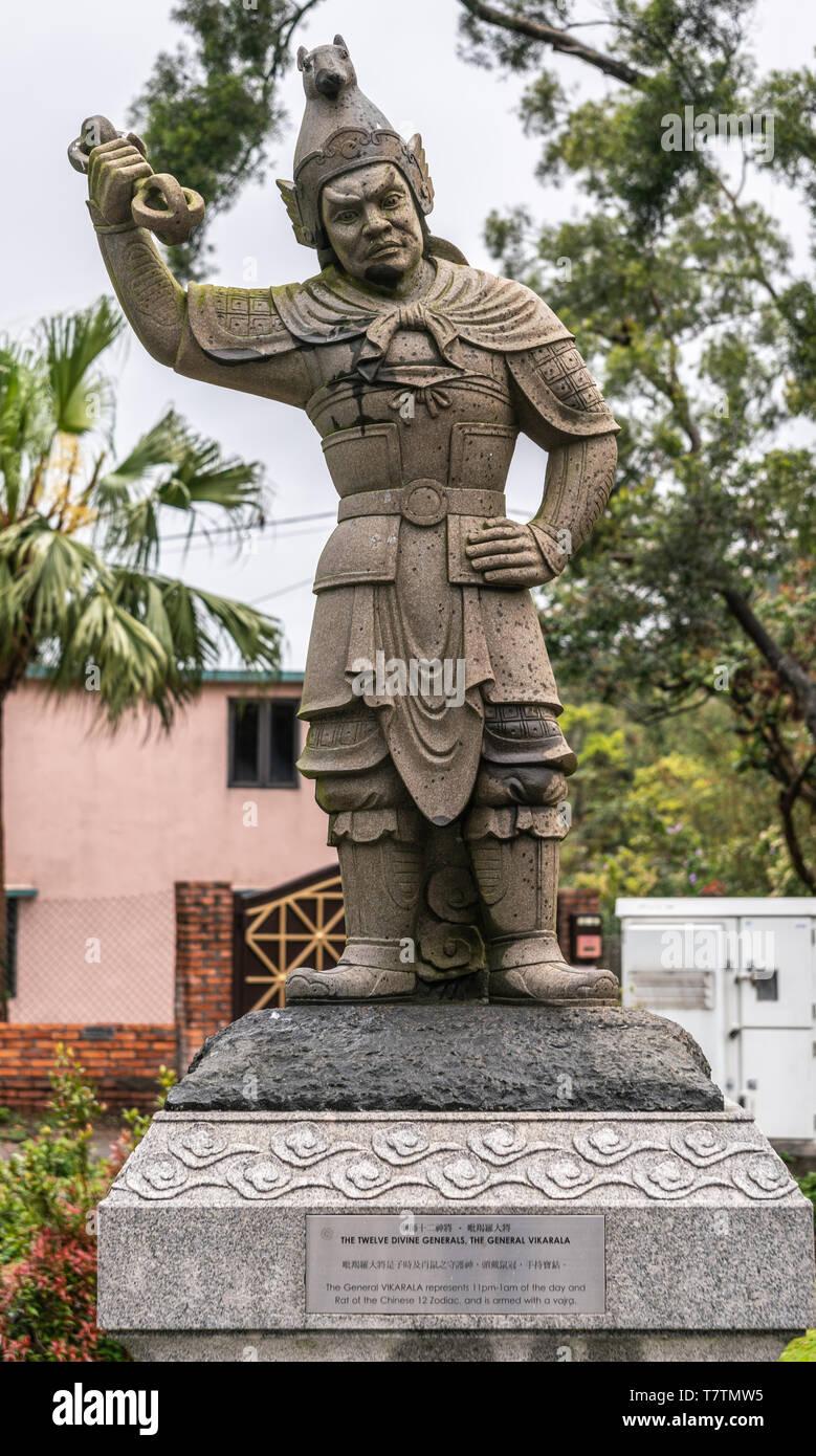 Hong Kong, China - March 7, 2019: Lantau Island. Po Lin Buddhist Monastery. Stone statue of General Vikarala, one of the twelve Divine Generals. Green - Stock Image