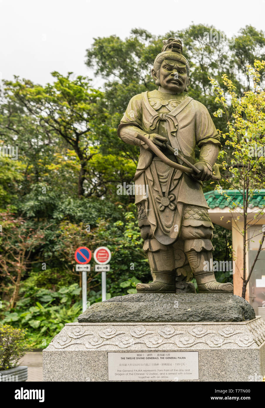Hong Kong, China - March 7, 2019: Lantau Island. Po Lin Buddhist Monastery. Stone statue of General Pajra, one of the twelve Divine Generals. Green fo - Stock Image