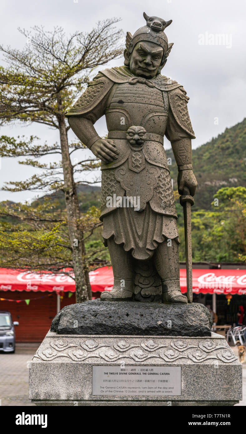 Hong Kong, China - March 7, 2019: Lantau Island. Po Lin Buddhist Monastery. Stone statue of General Catura, one of the twelve Divine Generals. Green f - Stock Image