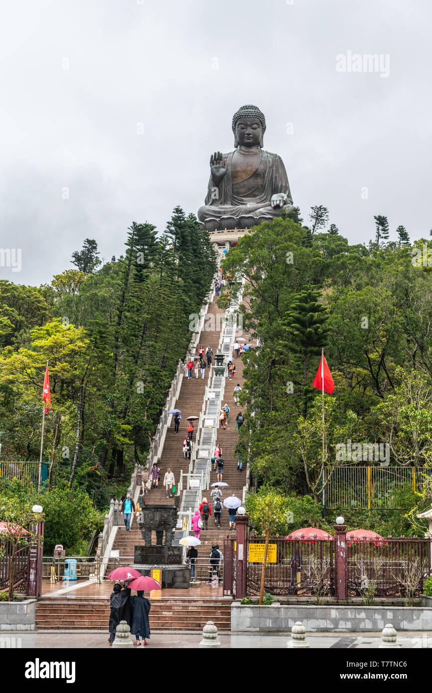Hong Kong, China - March 7, 2019: Lantau Island. Giant Tian Tan Buddha statue on top of tree covered hill with brown stairway under raining sky. Red f - Stock Image