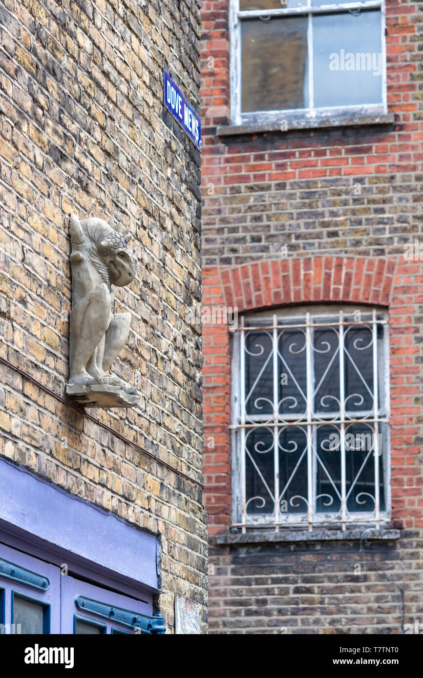 Stone griffin grotesque against a house brick wall. Dove Mews, South Kensington, SW7, London. England - Stock Image