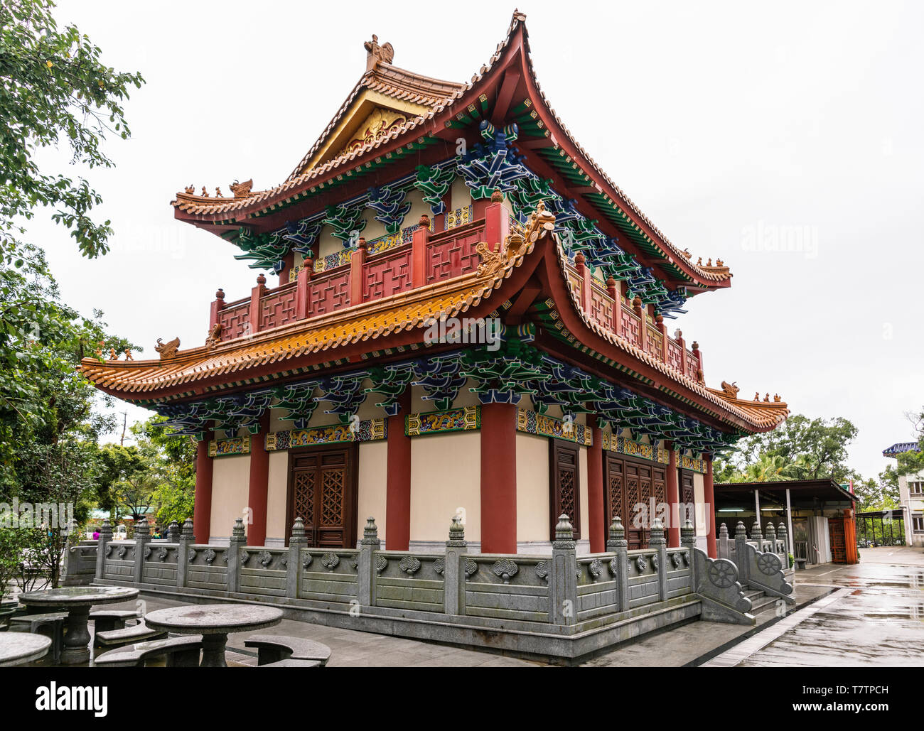 Hong Kong, China - March 7, 2019: Lantau Island. Po Lin Buddhist Monastery. Small red-roofed hall under silver sky. Some green foliage. Decorated wall - Stock Image