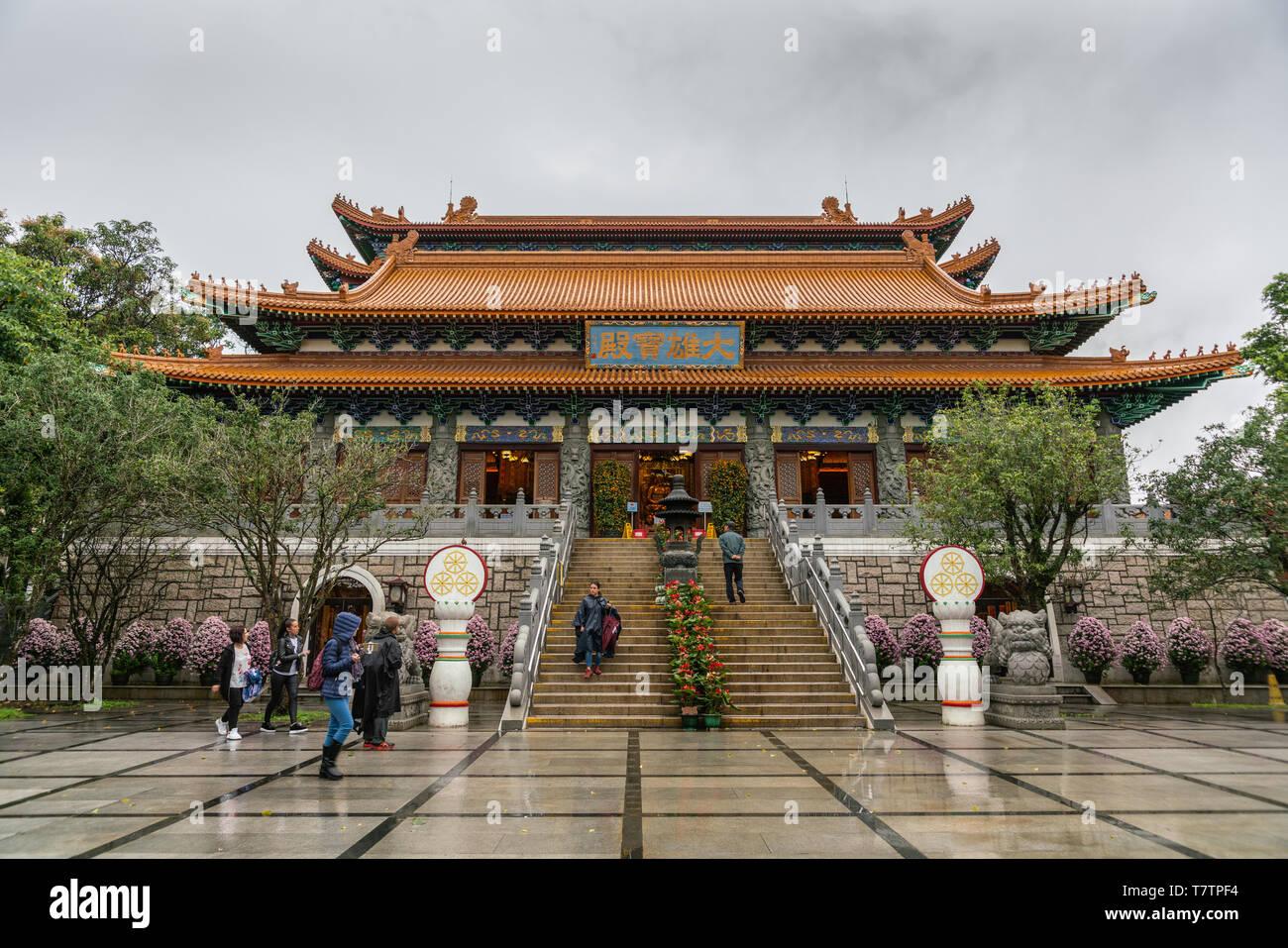 Hong Kong, China - March 7, 2019: Lantau Island. Po Lin Buddhist Monastery. large red-roofed prayer hall under silver sky. Some green foliage. Decorat - Stock Image