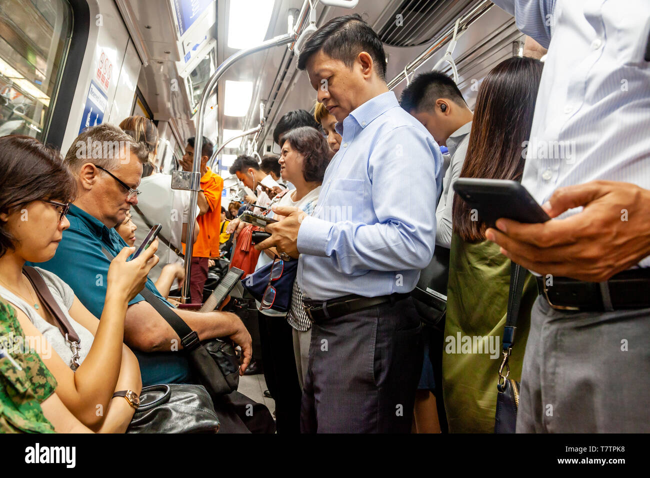 People Looking At Their Smartphones On The MRT, Singapore, South East Asia - Stock Image