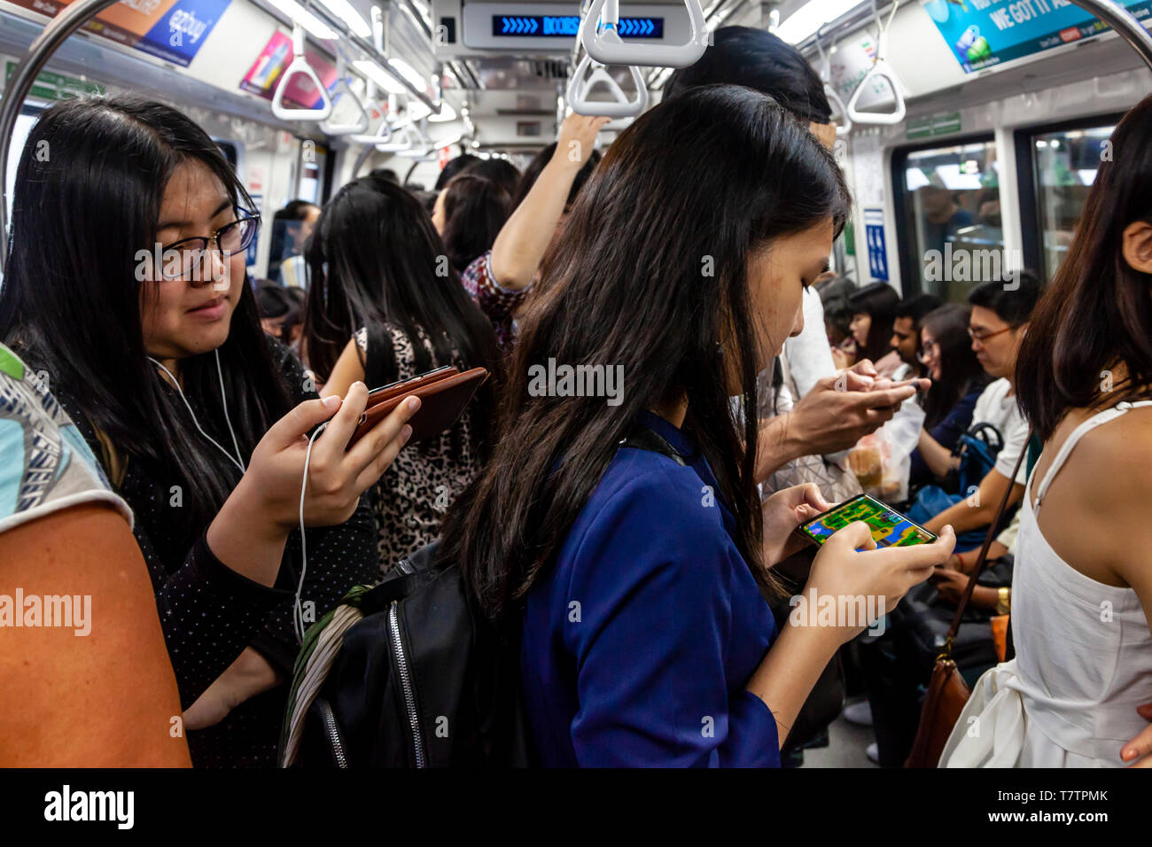 Young People Looking At Their Smartphones On The MRT, Singapore, South East Asia - Stock Image