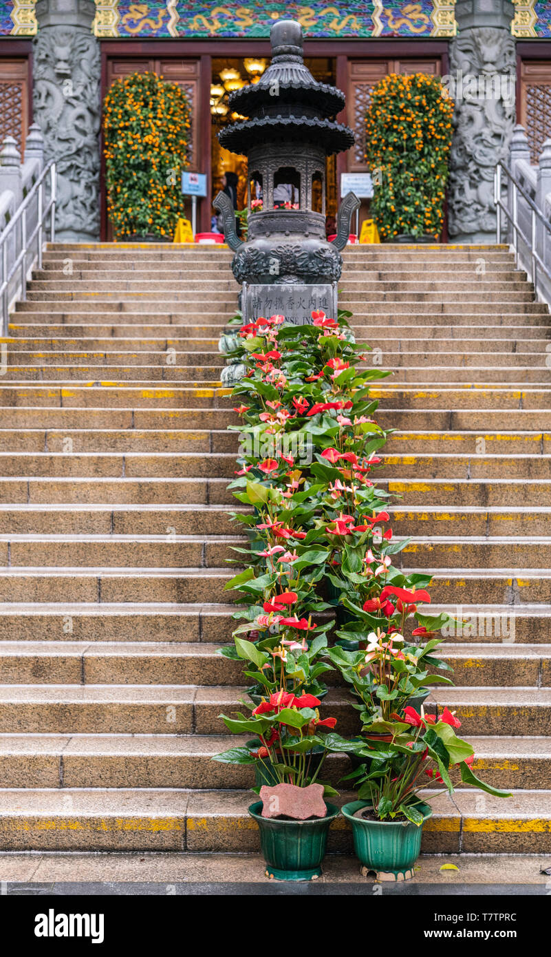 Hong Kong, China - March 7, 2019: Lantau Island. Po Lin Buddhist Monastery. Stairway to large red-roofed prayer hall. Some green foliage. Decorated wa - Stock Image