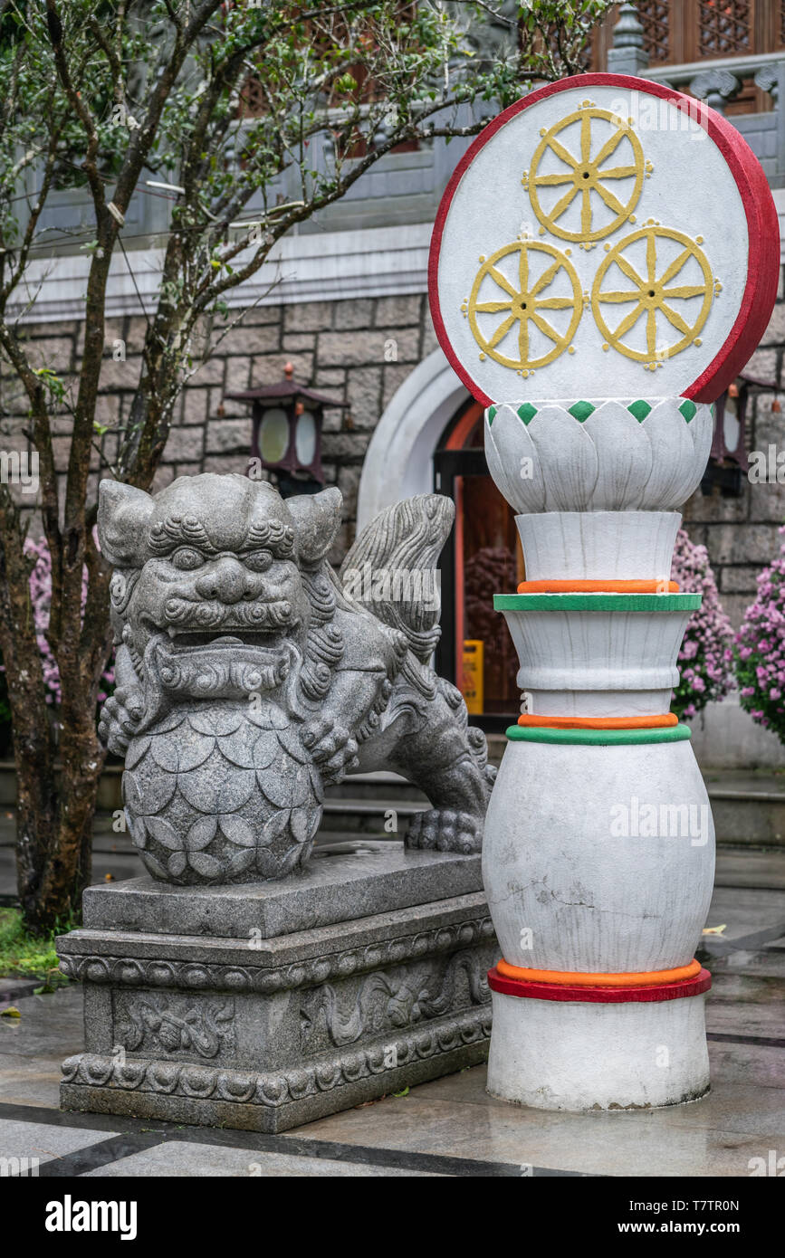 Hong Kong, China - March 7, 2019: Lantau Island. Po Lin Buddhist Monastery. Gray stone Lion monster and white-red-gold decoration at stairway to large - Stock Image