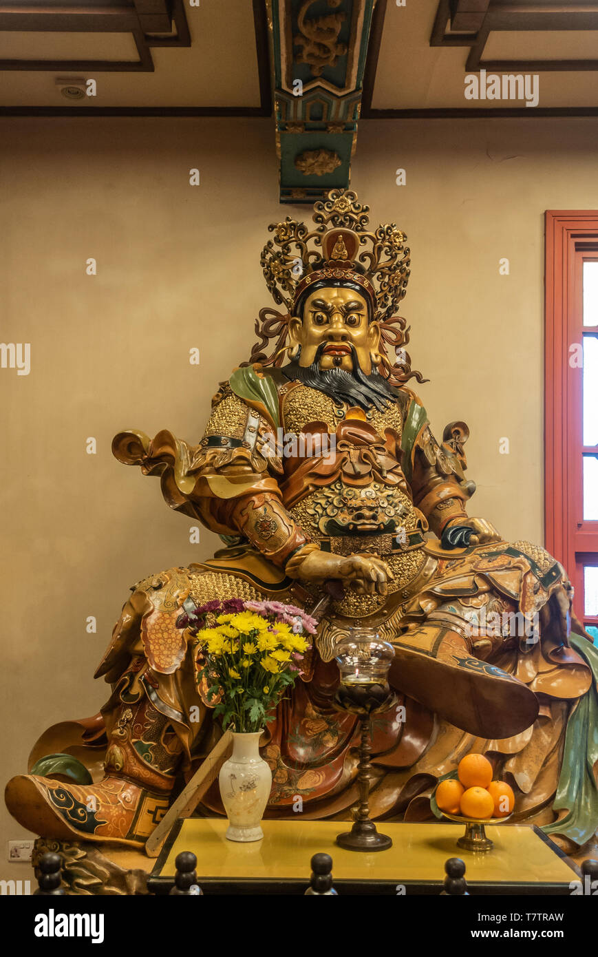 Hong Kong, China - March 7, 2019: Lantau Island. Po Lin Buddhist Monastery. Extensively decorated statue of South heavenly king Virudhaka offers shade - Stock Image