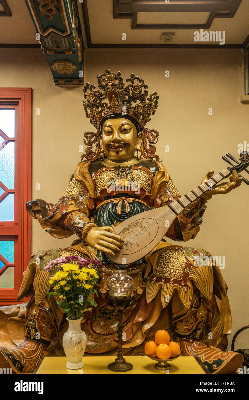 Hong Kong, China - March 7, 2019: Lantau Island. Po Lin Buddhist Monastery. Extensively decorated statue of East heavenly king Dhrtarastra offers shad - Stock Image