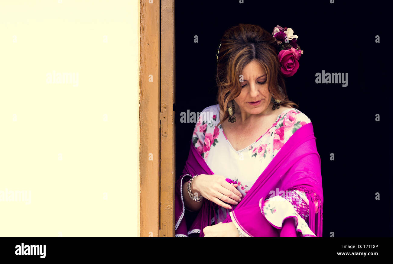 A Spanish woman wearing a bright white traditional flamenco style dress in Andalusia standing in front of a door with white background for copy space - Stock Image