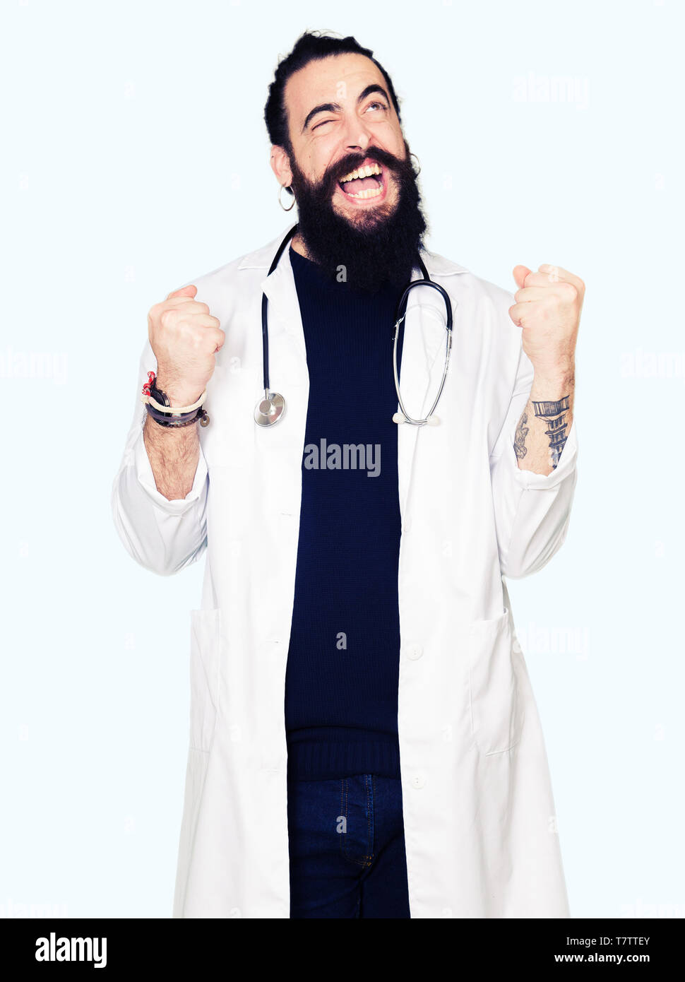Doctor with long hair wearing medical coat and stethoscope very happy and excited doing winner gesture with arms raised, smiling and screaming for suc Stock Photo
