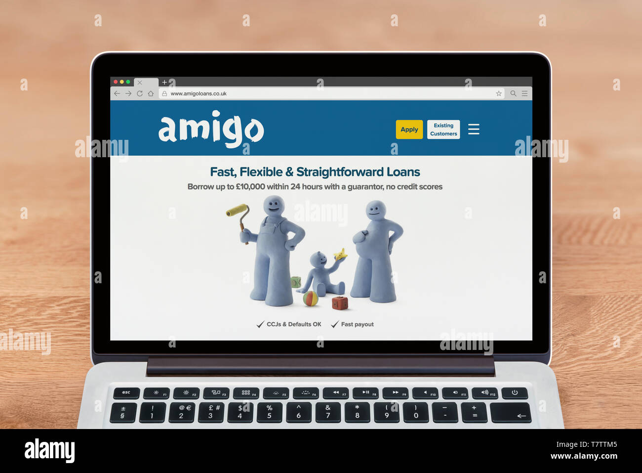 An Apple Macbook displays the Amigo Loans website (Editorial use only). - Stock Image