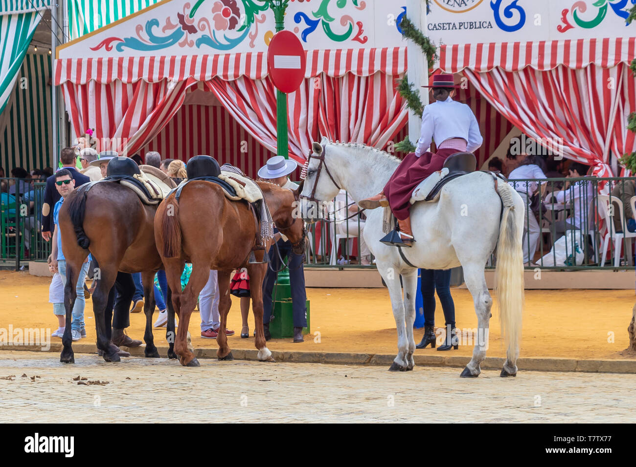 Seville, Spain - May 5, 2019: People riding horses and celebrating Seville's April Fair, Seville Fair (Feria de Sevilla). The Seville April Fair on Ma - Stock Image