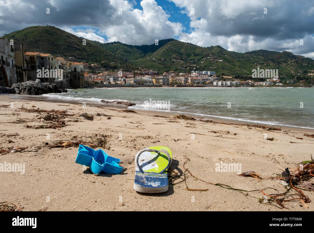 Flip flop and seaweed washed up on the beach at Cefalu, Sicily. - Stock Image