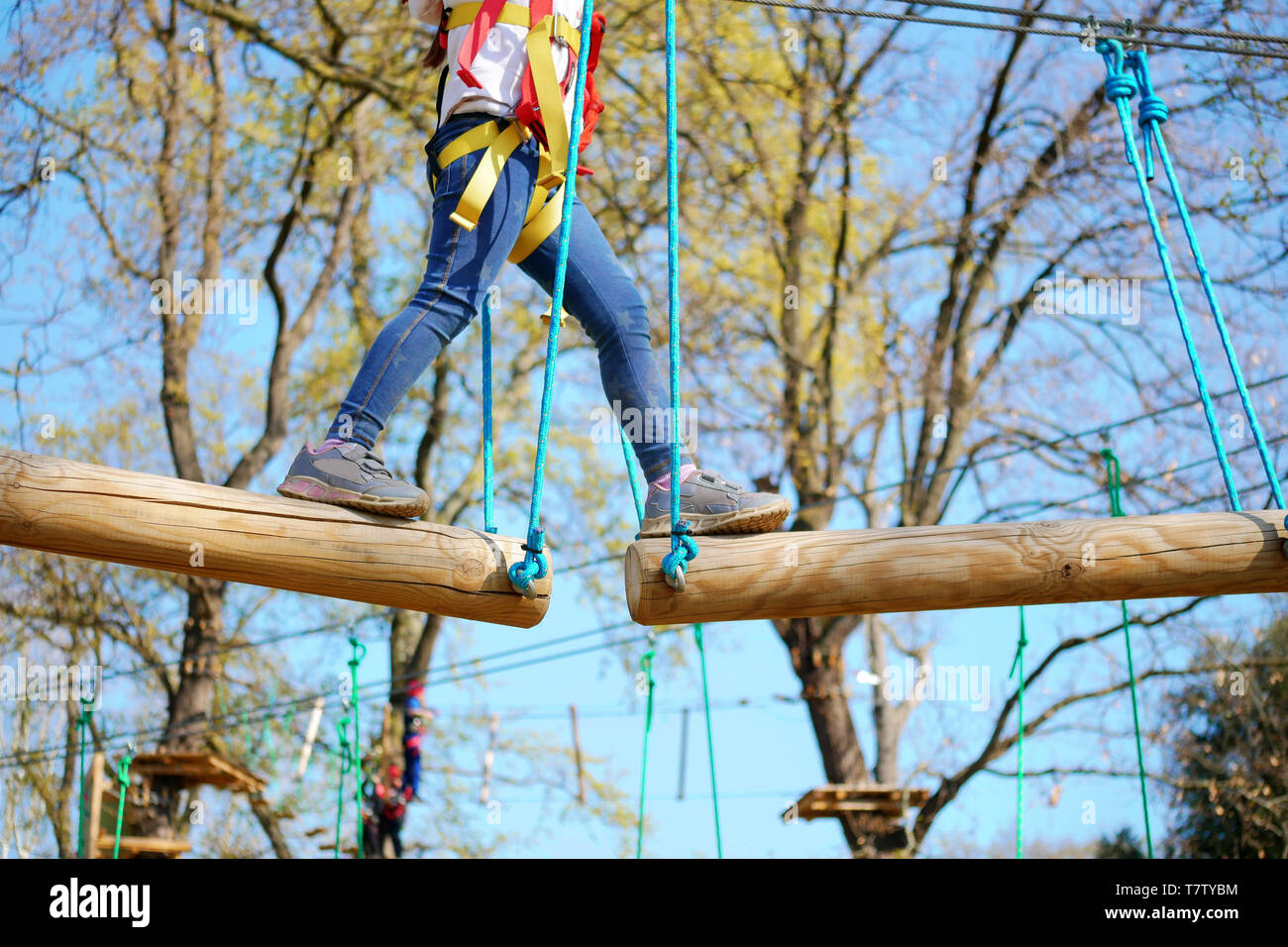 Closeup Little girl playing at adventure park climbing and addressing balance challenges for self esteem - Stock Image