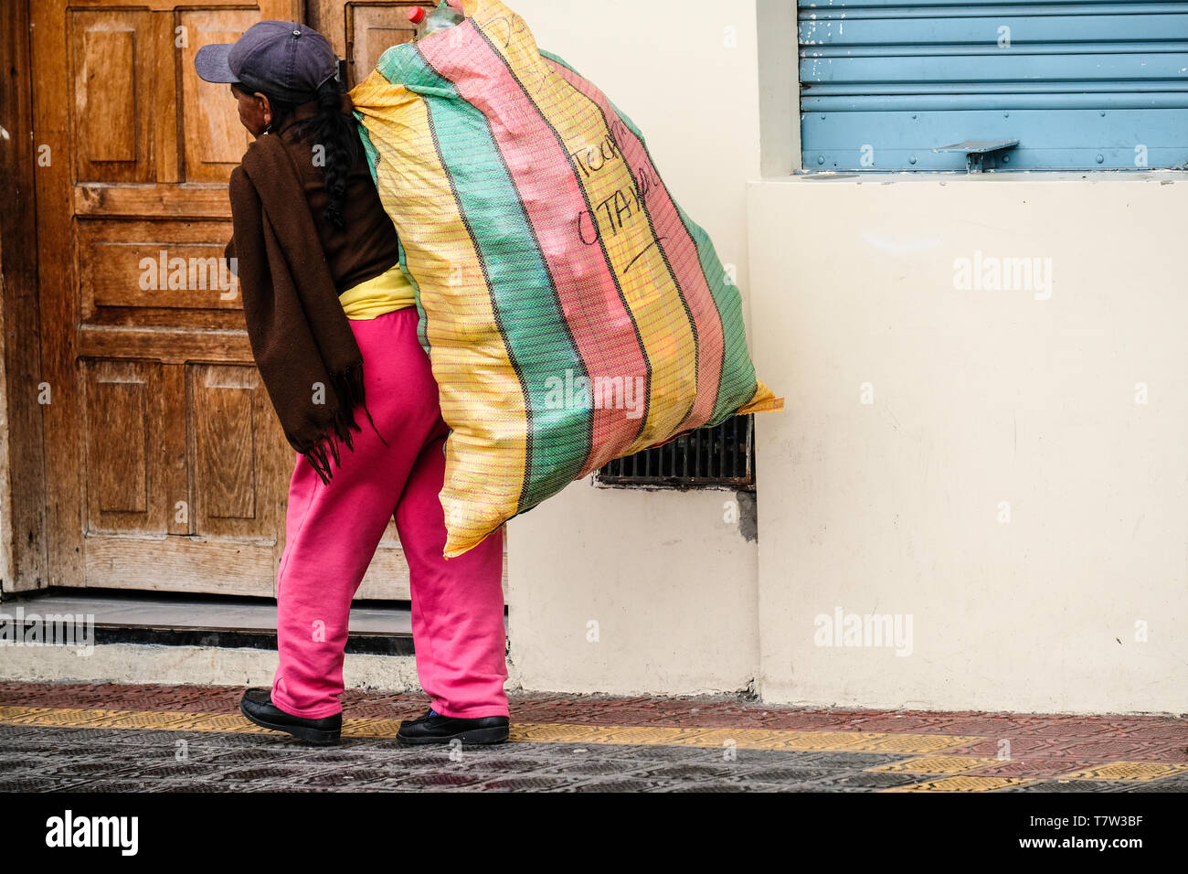 An old indigenous woman carrying a big heavy bag on her back at Octaval Market in Ecuador - Stock Image