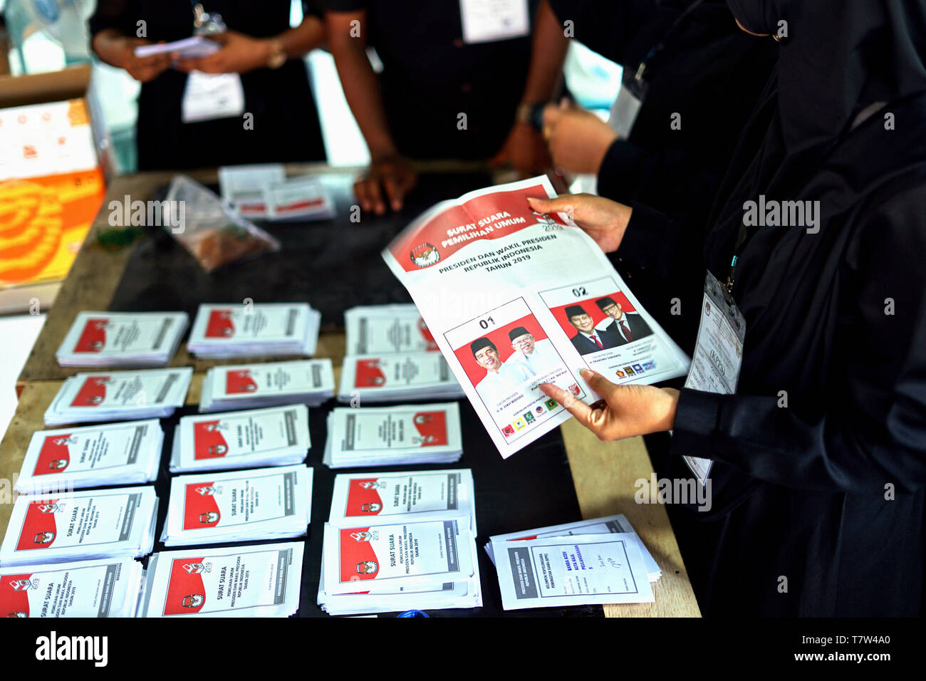 An election officer holds up the ballot during vote count at a polling station after the general election in Banda Aceh, Indonesia - Stock Image