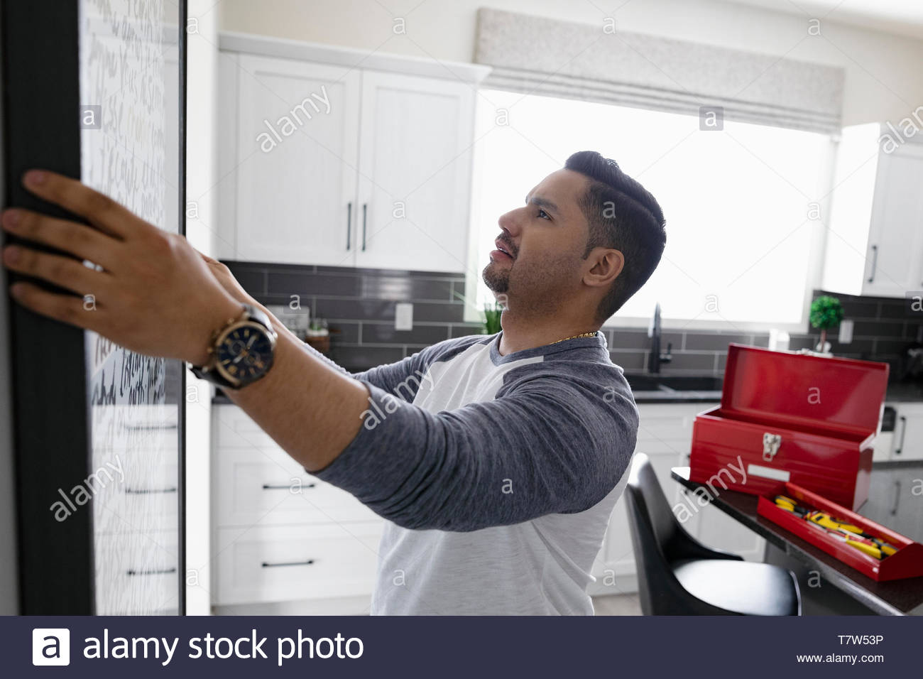 Man hanging picture frame on kitchen wall - Stock Image