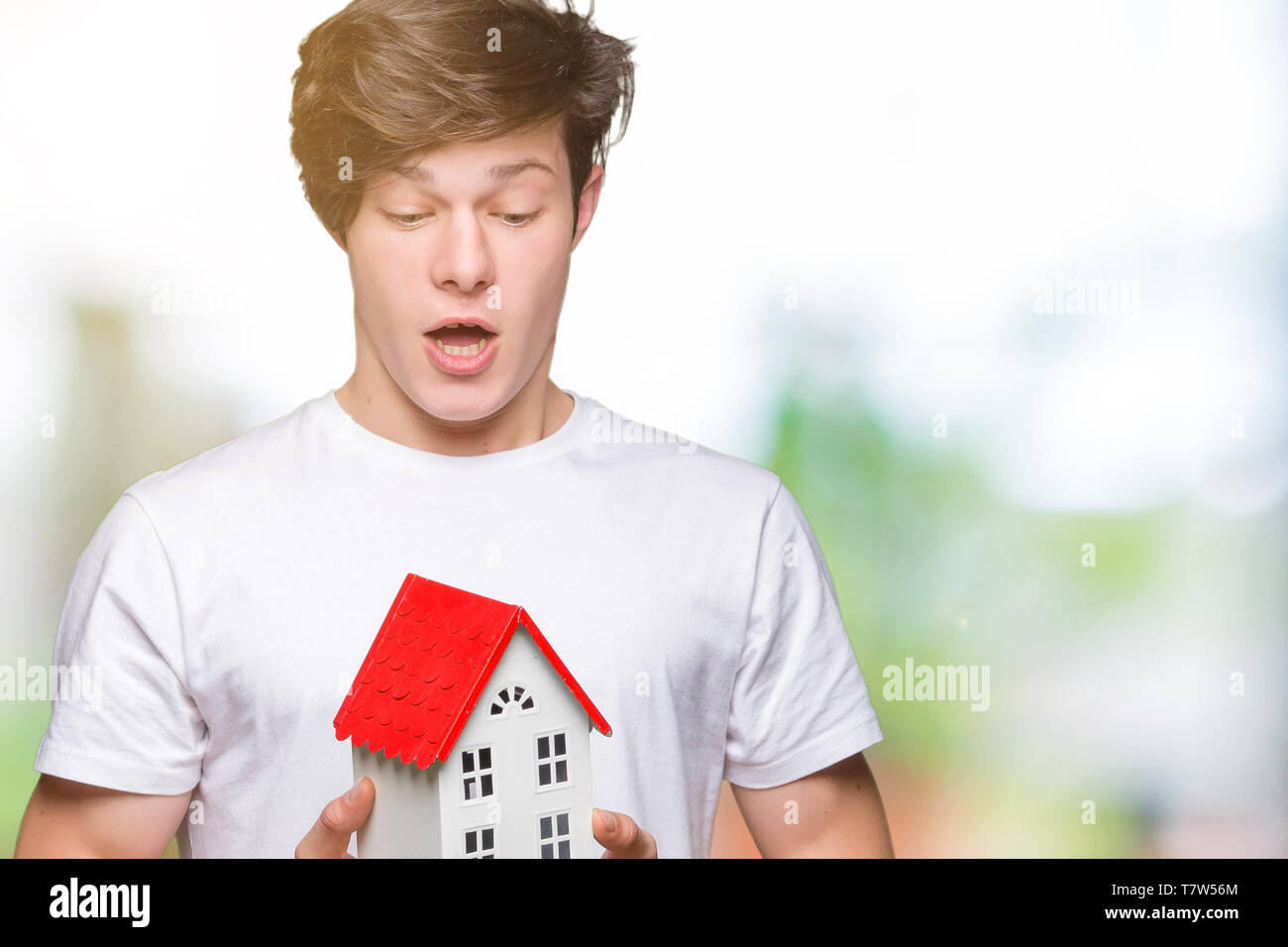 Young man holding house over isolated background scared in shock with a surprise face, afraid and excited with fear expression - Stock Image