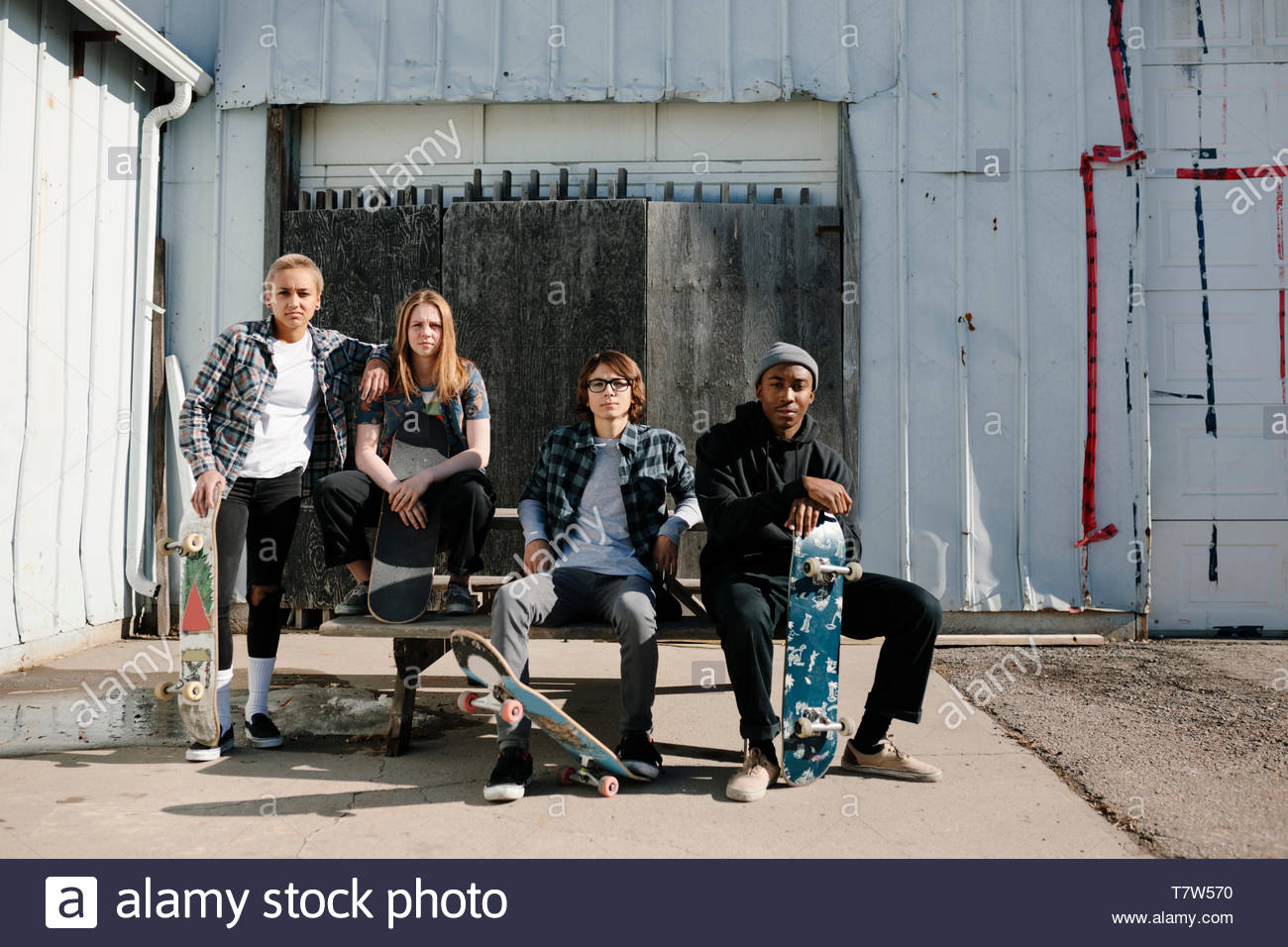 Portrait confident, cool young skateboarder friends in sunny parking lot - Stock Image