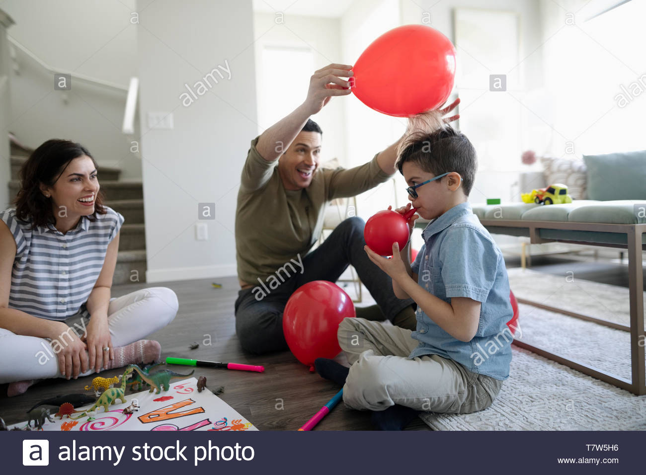 Playful father with balloon creating static with son's hair - Stock Image