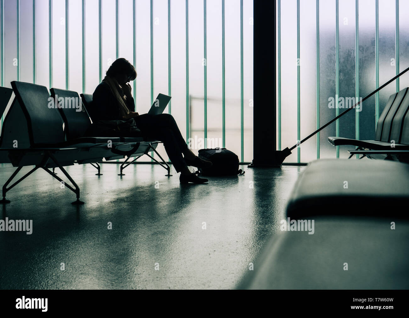 Side view of thinkful business woman working in empty airport terminal on thin laptop computer waiting for the delayed plane preparing working documents presentation - Stock Image