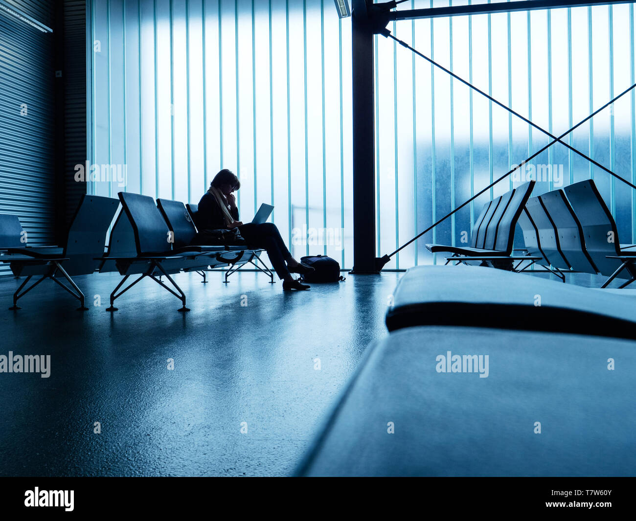 Wide airport terminal interior with glass wall and one business woman working on thin laptop computer waiting for the delayed plane preparing working documents presentation - Stock Image