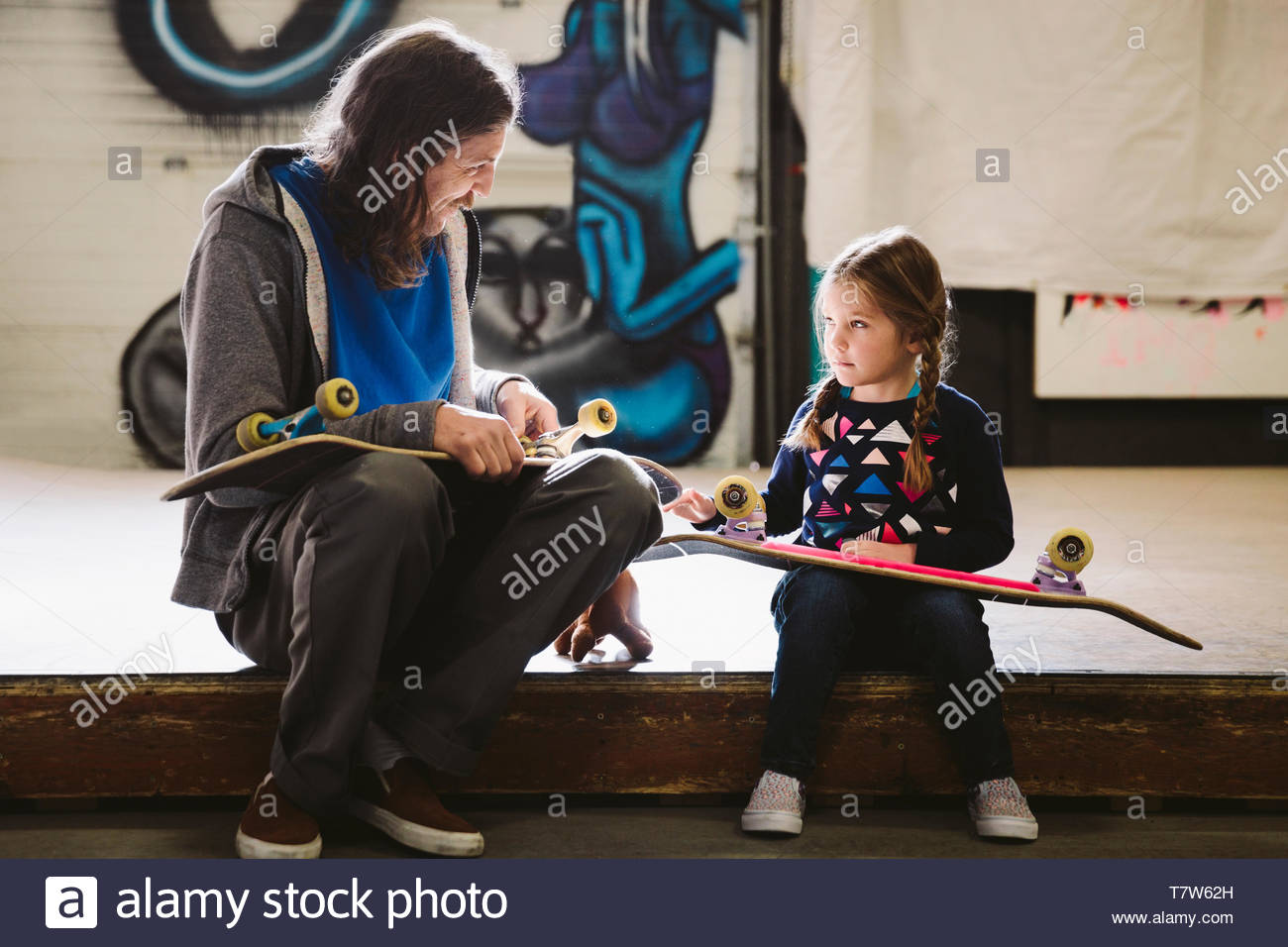 Father and daughter at indoor skate park - Stock Image