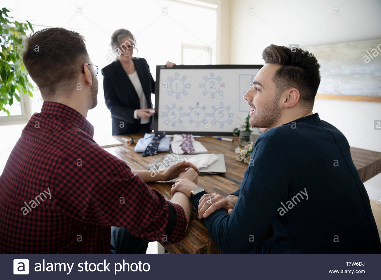 Affectionate gay male couple meeting with wedding planner, deciding on seating arrangements - Stock Image