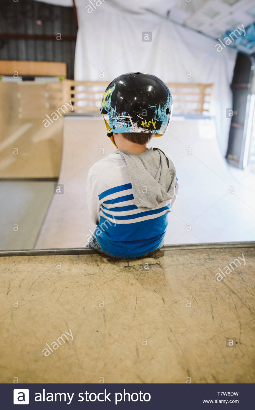 Boy sitting at top of ramp at indoor skate park - Stock Image
