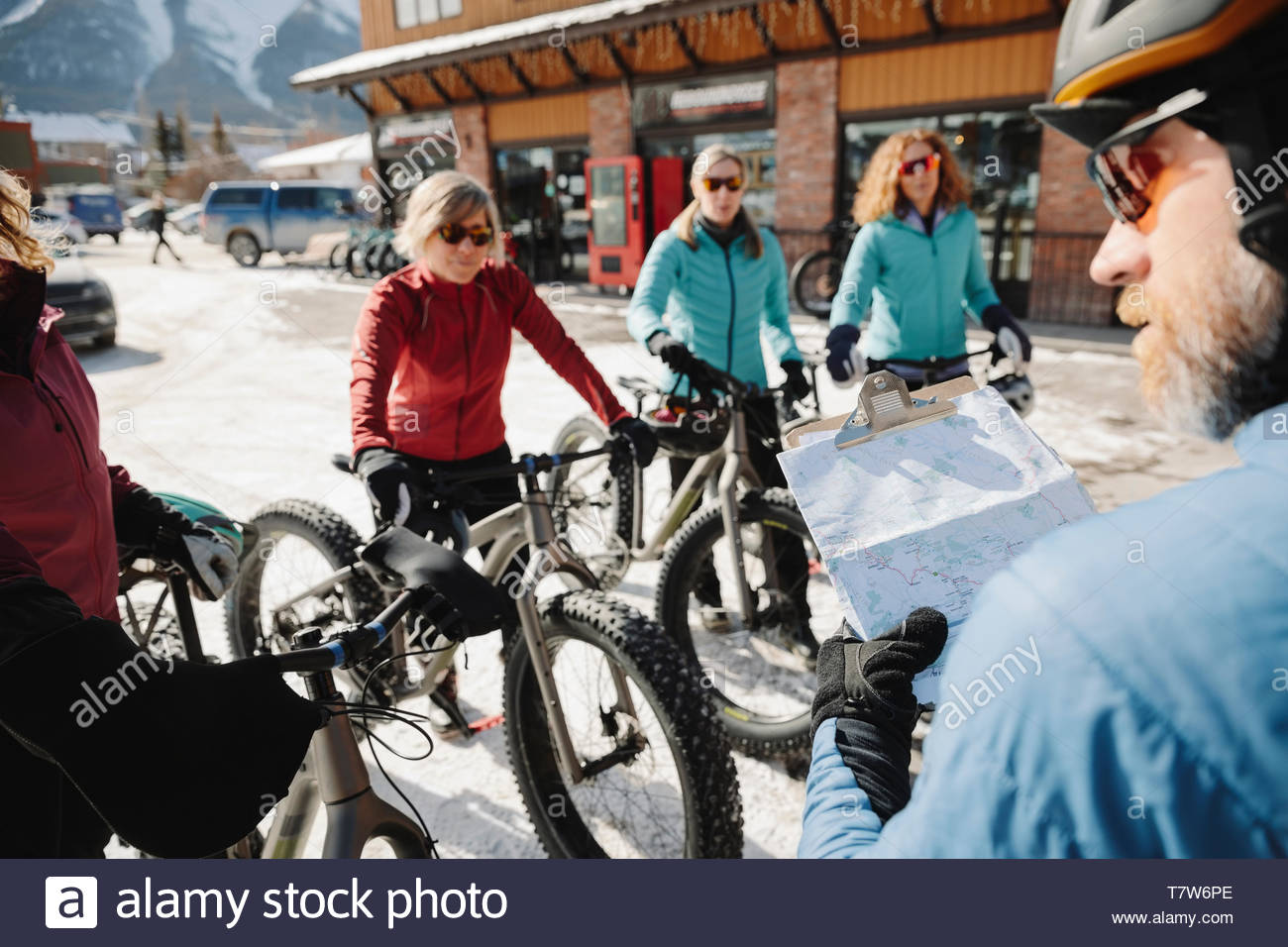 Instructor guiding friends fat biking in snow - Stock Image