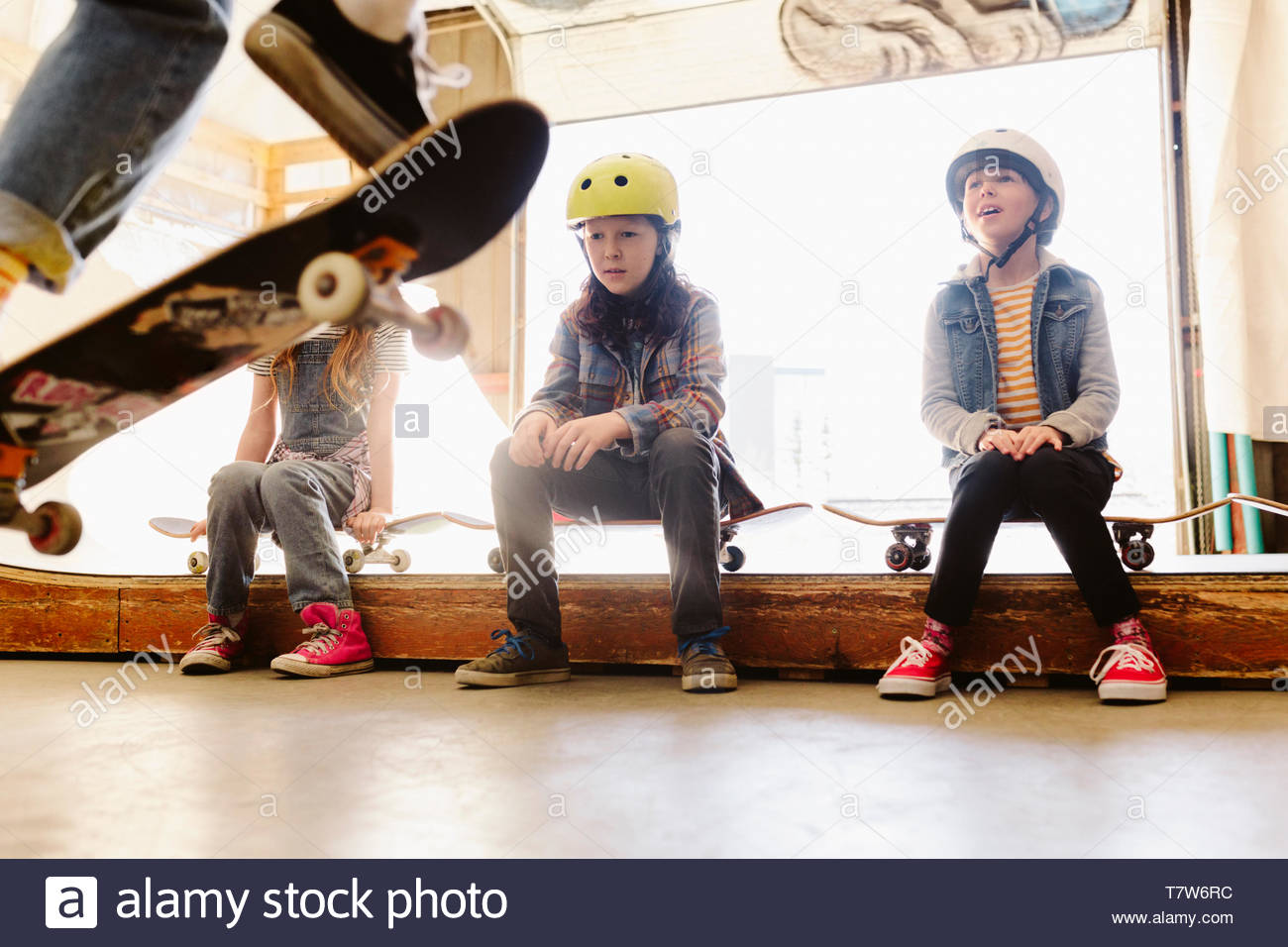 Kids watching at indoor skate park - Stock Image