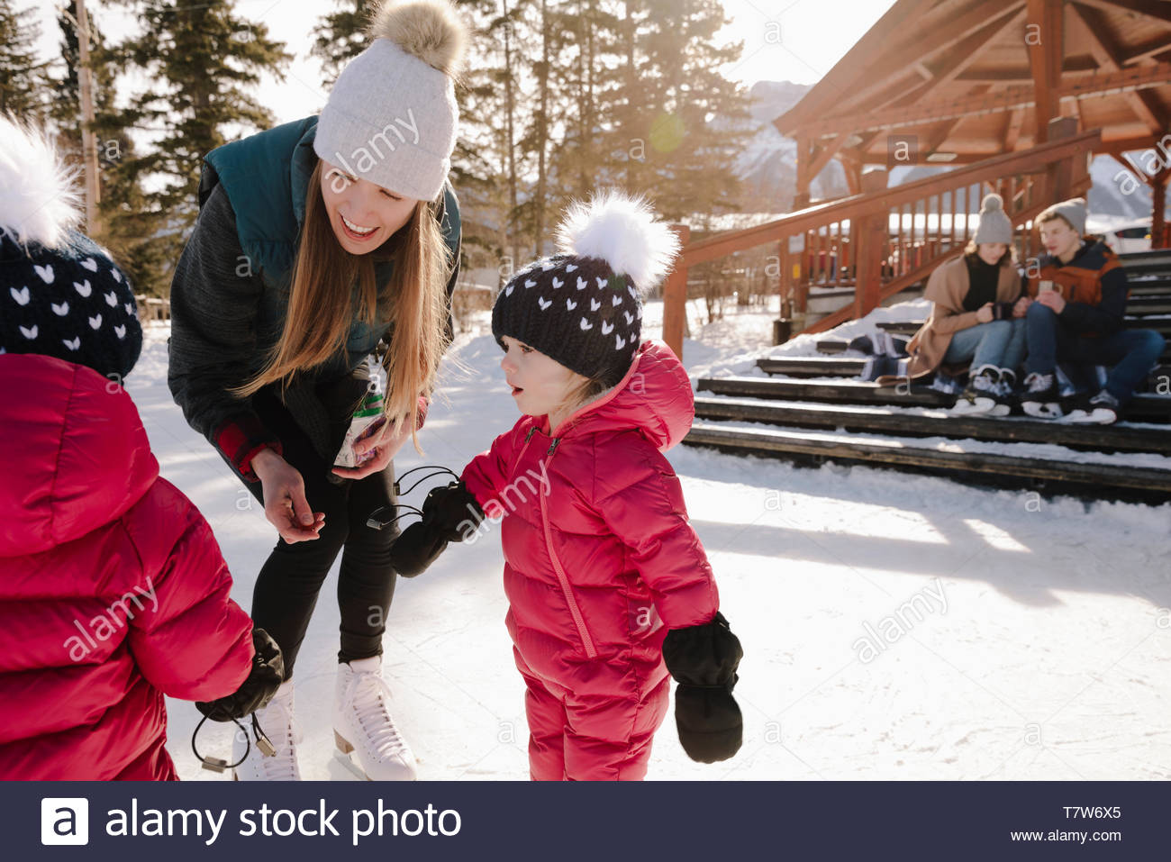 Mother and toddler daughters ice skating outdoors - Stock Image