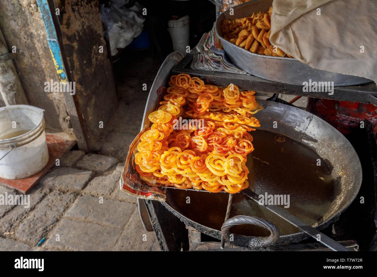 Street scene, Mahipalpur district, a suburb near Delhi Airport in New Delhi, capital of India: Indian sweet, crispy golden deep fried jalebi - Stock Image