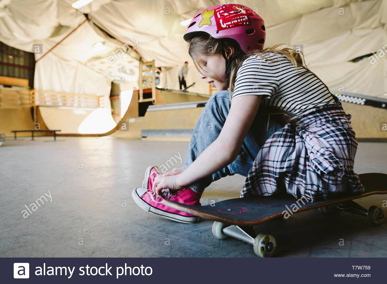 Girl tying shoelace on skateboard at indoor skate park - Stock Image