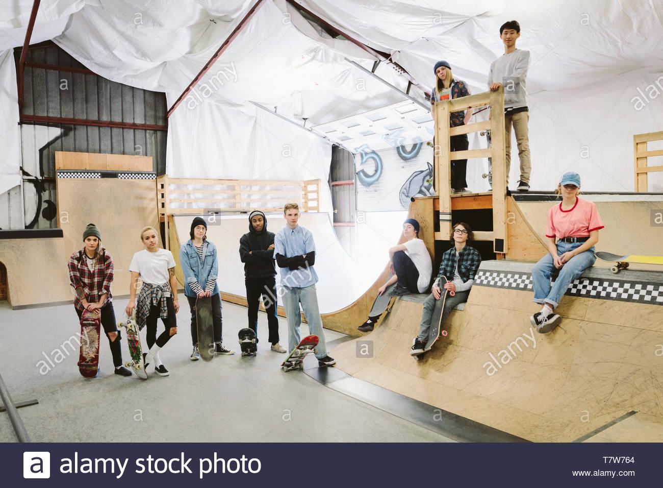 Portrait confident young friends skateboarding at indoor skate park - Stock Image