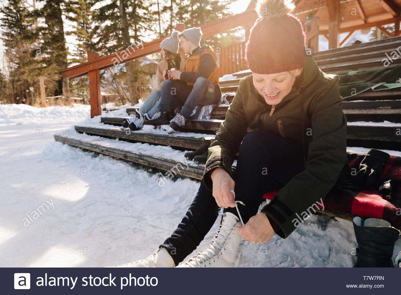 Smiling senior woman tying ice skates on snowy steps - Stock Image