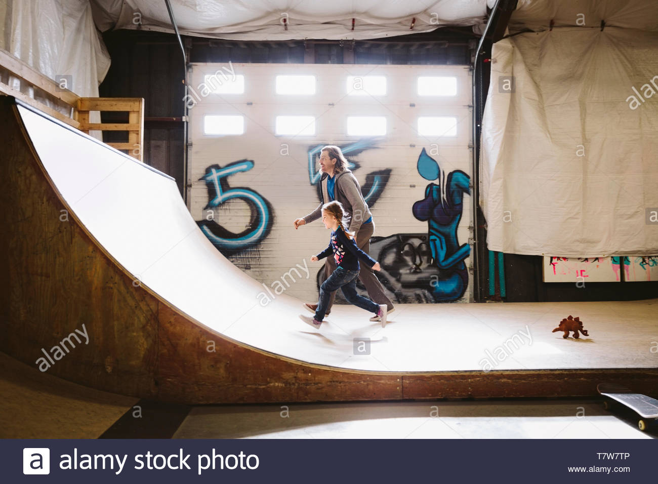 Father and daughter running up indoor skate park ramp Stock Photo
