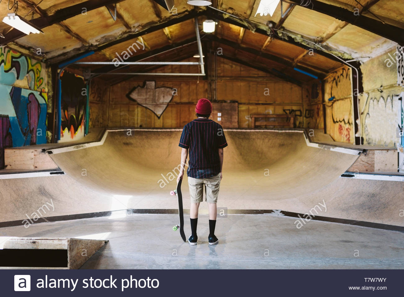 Young male skateboarder at indoor skate park - Stock Image