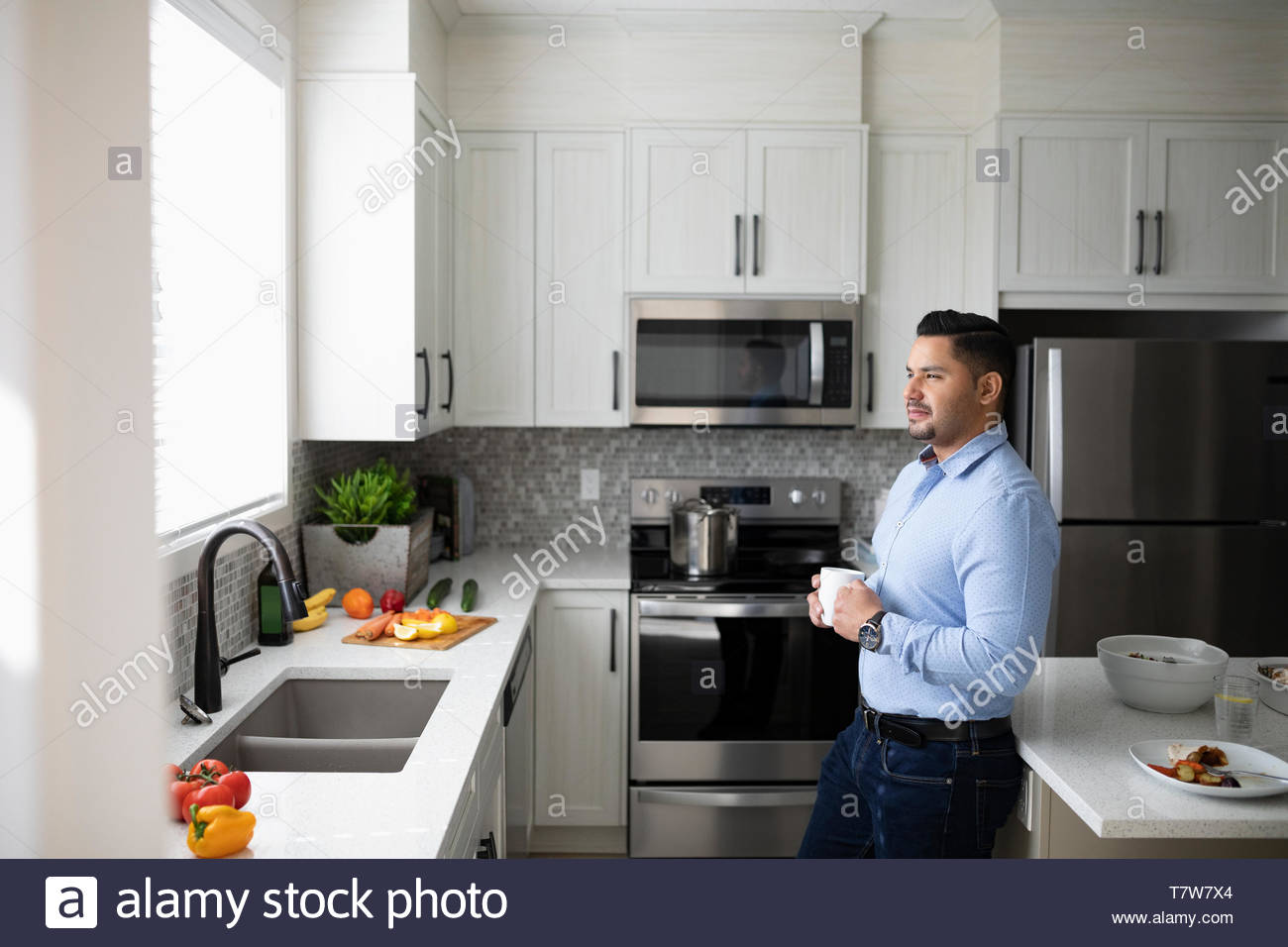 Thoughtful man drinking coffee and looking out kitchen window - Stock Image
