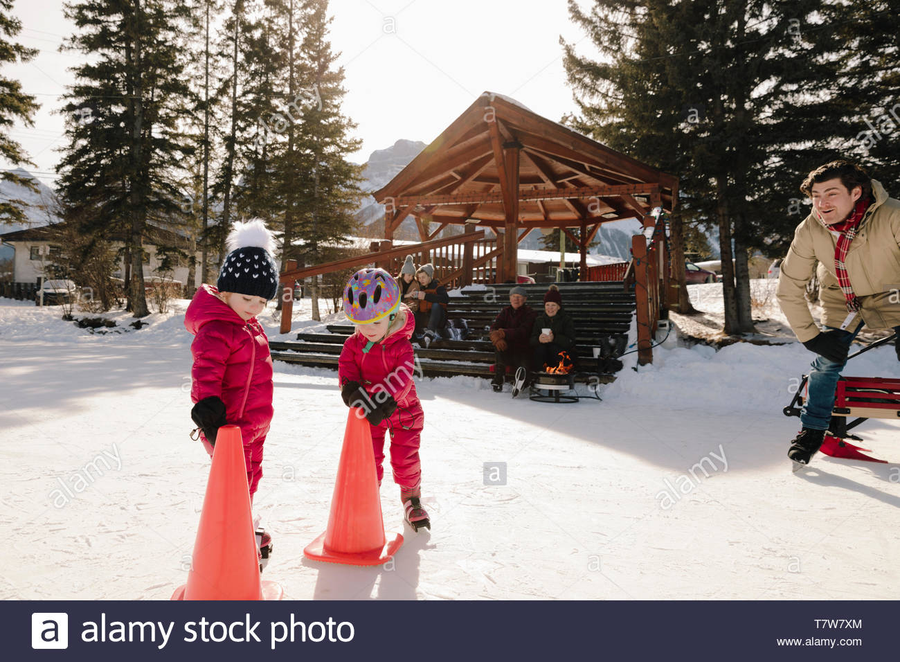 Father and toddler daughters ice skating on frozen pond - Stock Image