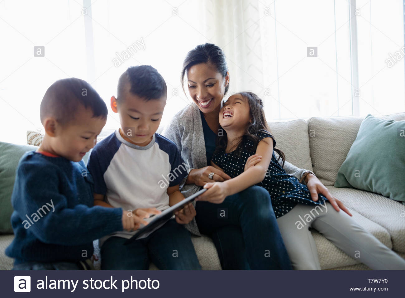 Happy mother and children using digital tablet on living room sofa - Stock Image