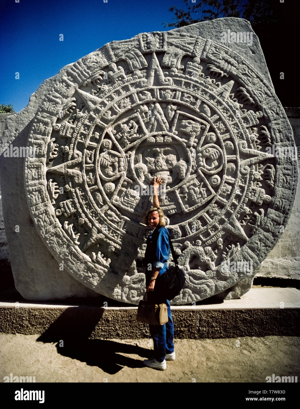 A woman tourist points to the face of the Aztec sun god that is the center of this replica of a major Mexican archaeological discovery of a massive carving known as the Aztec calendar stone on display in La Paz, the capital of Baja California Sur in Mexico, North America. Also called the Aztec sun stone, the original basalt disk was found in Mexico City in 1790. Hieroglyphics on the circular monolith relate the mythology of the re-creation of the Aztecan world in the 16th Century. - Stock Image