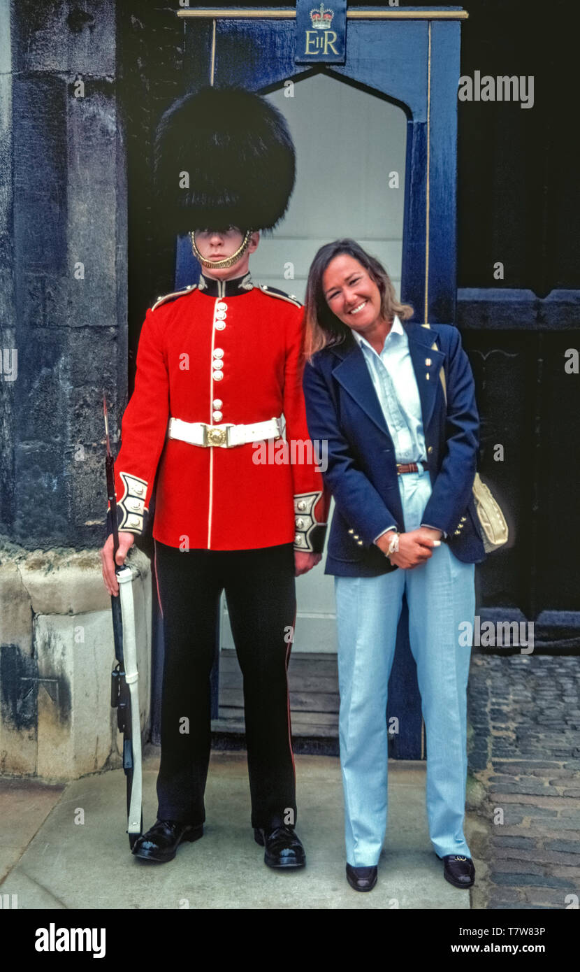 A Queen's Guard in the traditional red tunic and black bearskin hat keeps his composure as a female tourist snuggles up to him for a souvenir photograph in front of his sentry box at St. James's Palace in London, England. Since 2014 the guards and their sentry boxes have been relocated inside gates to the palace and tourists are no longer able to pose beside them. Also, the guards nowadays carry the British Army's standard-issue automatic assault rifles instead of the type of gun seen in this historical 1981 photograph. Stock Photo