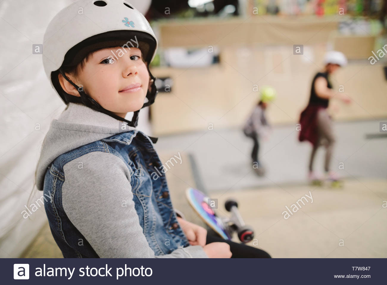 Portrait confident girl at indoor skate park - Stock Image