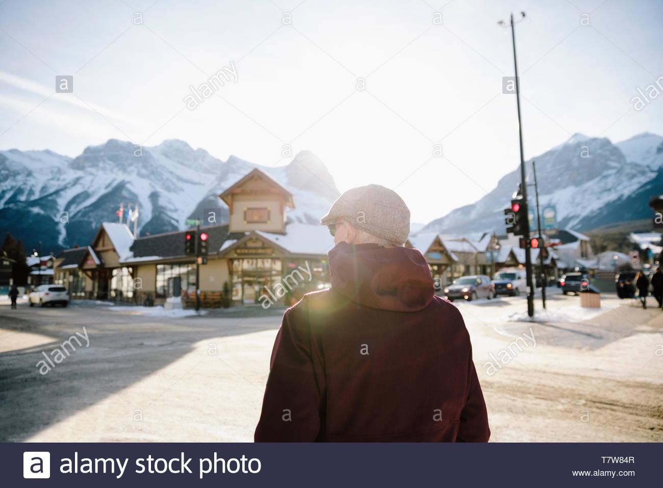 Man walking on sunny street in winter mountain town - Stock Image