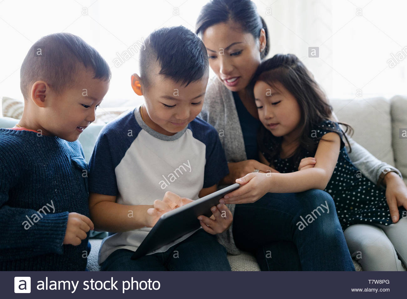 Mother and children using digital tablet on sofa - Stock Image