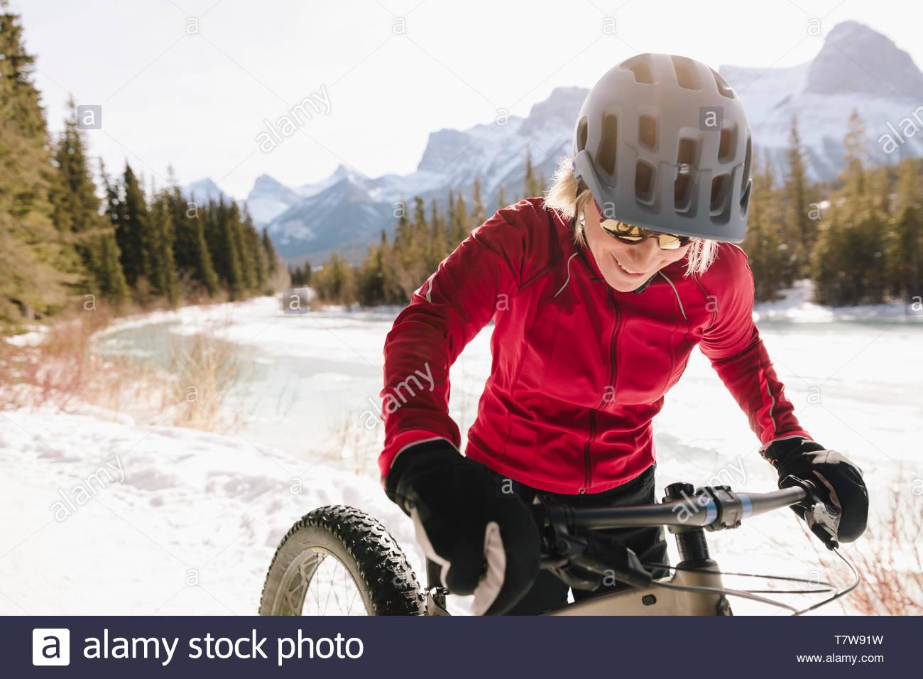 Smiling woman fat biking on snowy mountain trail - Stock Image